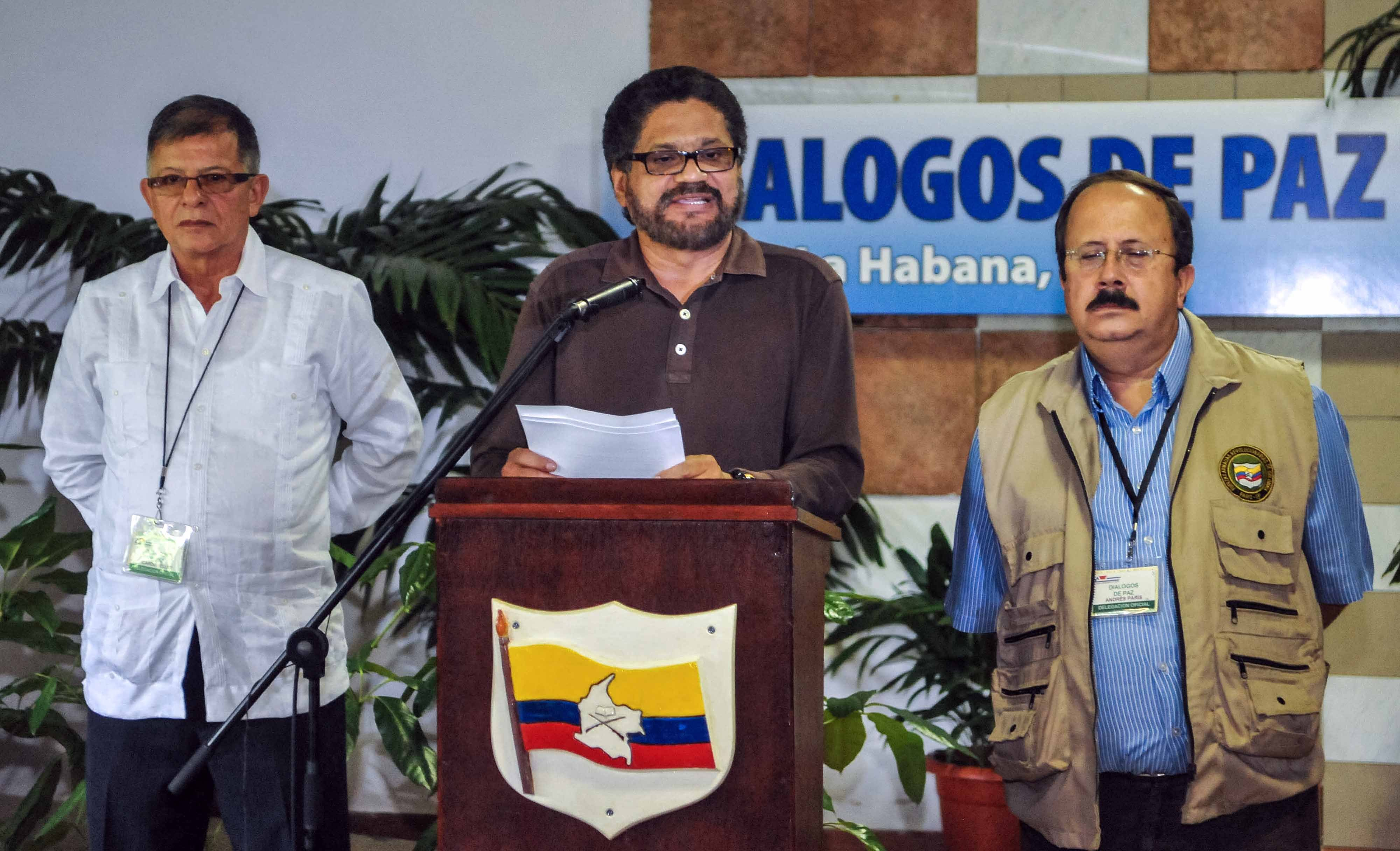 Commander Ivan Marquez (C), head of the Revolutionary Armed Forces of Colombia (FARC-EP) leftist guerrillas delegation for the peace talks with the Colombian government, reads a document to the media next to Commander Rodrigo Granda (L), and Commander Andres Paris at the Convention Palace in Havana on October 3, 2013, at the end of a new round of meetings with the Colombian government delegation. The Colombian government resumed peace talks with leftist rebels Thursday in a renewed bid to end nearly half a century of armed conflict. Negotiations, which began in November, picked up again in the Cuban capital following a two-week break.    AFP PHOTO/ADALBERTO ROQUE